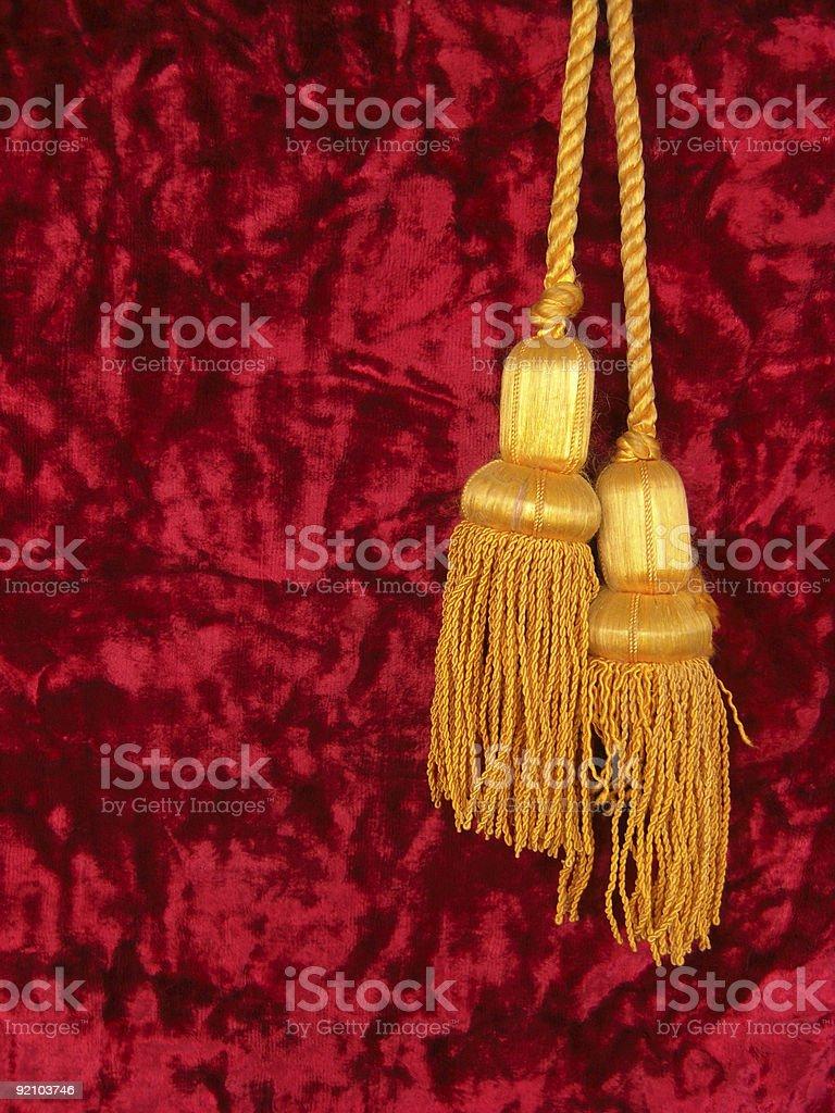 Red velvet with two golden tassels stock photo
