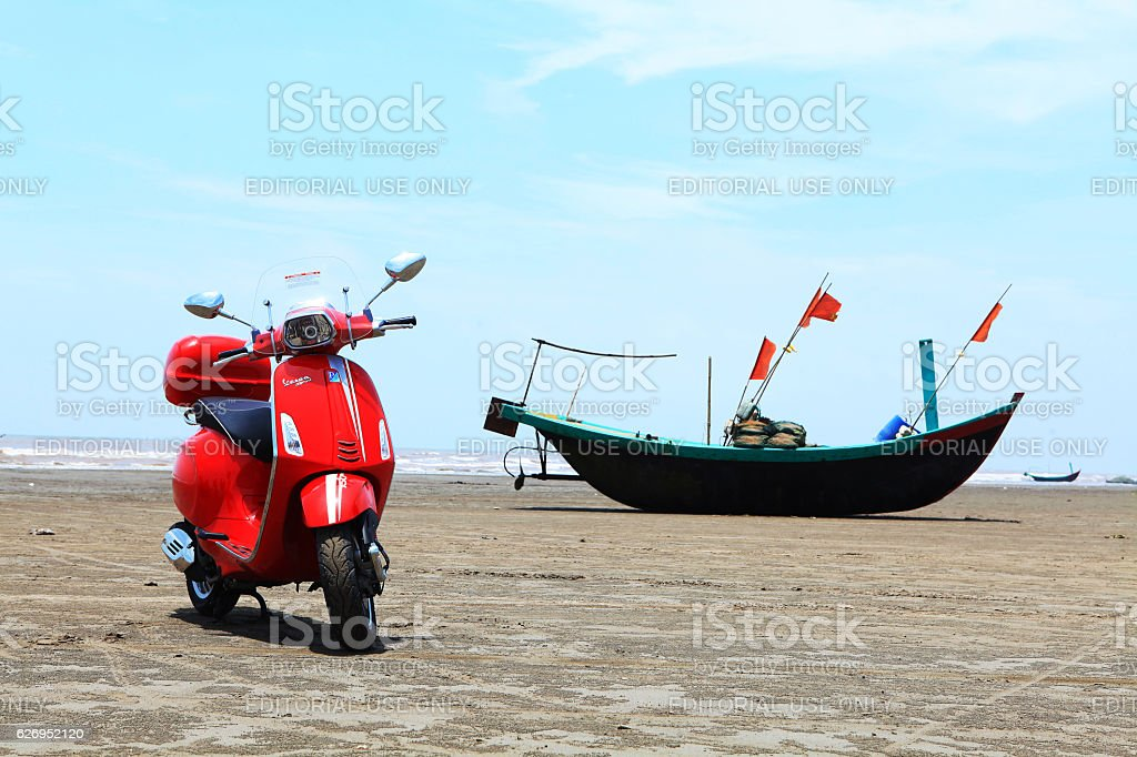 Red Vespa motorcycle on the beach stock photo