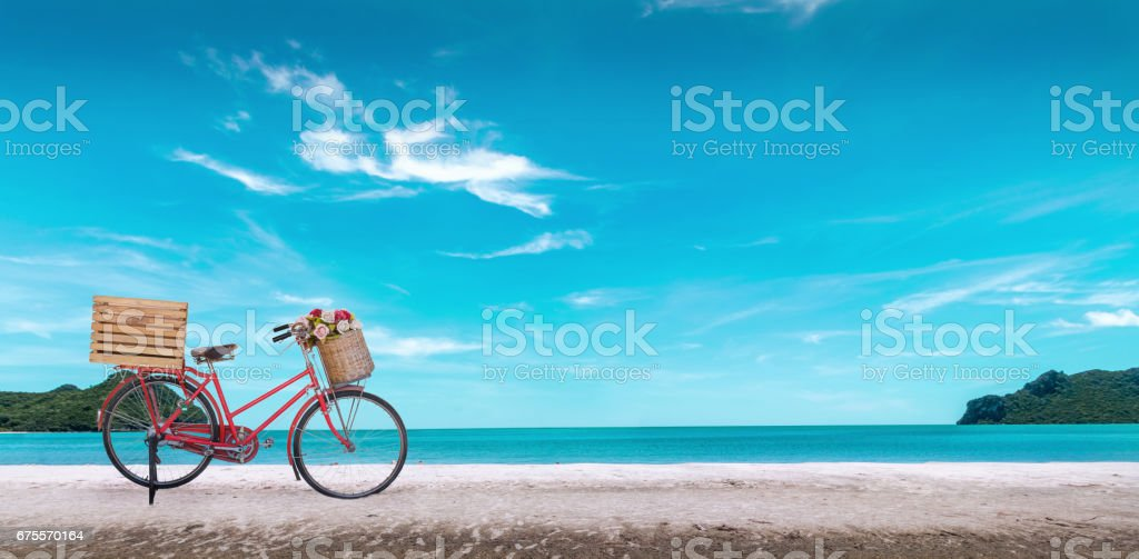 Red vintage bicycle on white sand beach over blue sea and clear blue sky background, spring or summer holiday vacation concept. stock photo