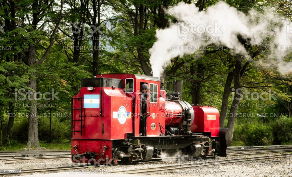 Red vintage steam locomotive moving along railroad tracks. March 25, 2013 - Ushuaia, Argentina stock photo