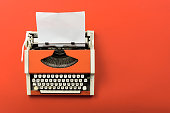 Red vintage typewriter with white blank paper sheet