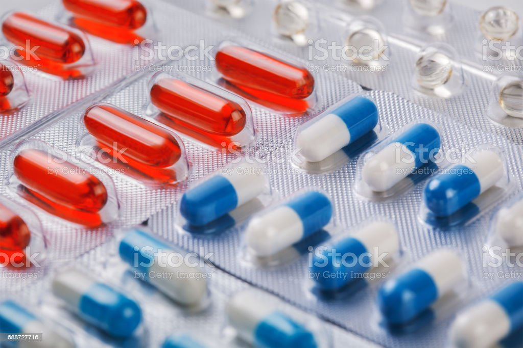 Red vitamin pills in plastic bag with other pills stock photo