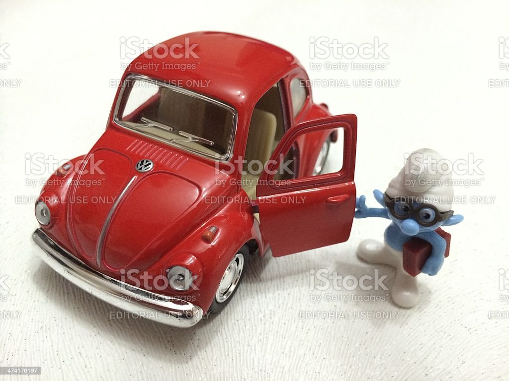 Red Volkswagen Beetle with Brainy toy character of Smurfs stock photo