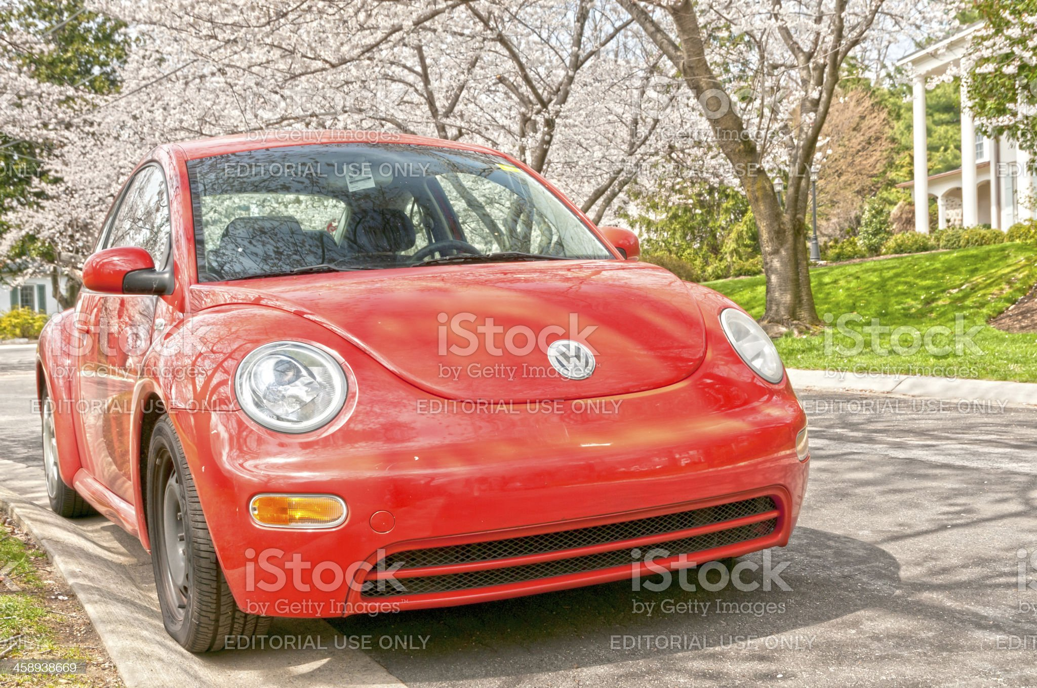 Red Volkswagen New Beetle under blooming trees royalty-free stock photo