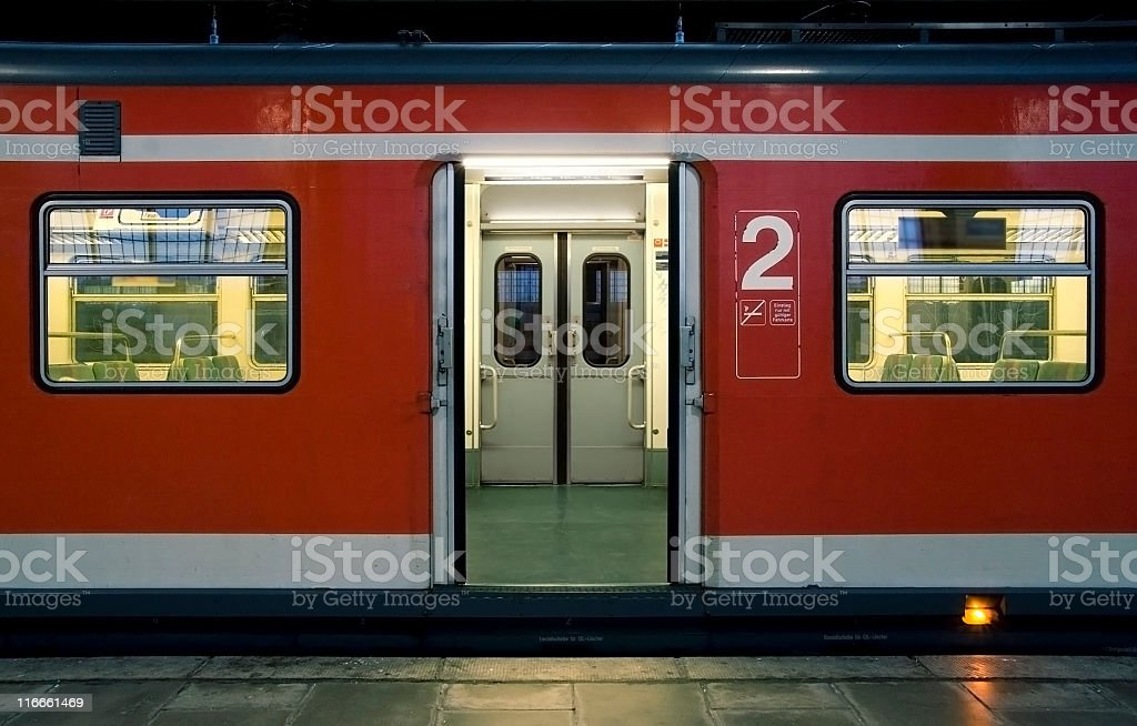 Red waiting train with doors open. Railroad station platfrom royalty-free stock photo