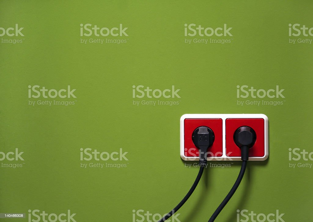 Red wall outlets with black plugs against a green background stock photo