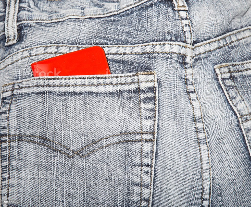 Red wallet in a hip-pocket of blue jeans stock photo