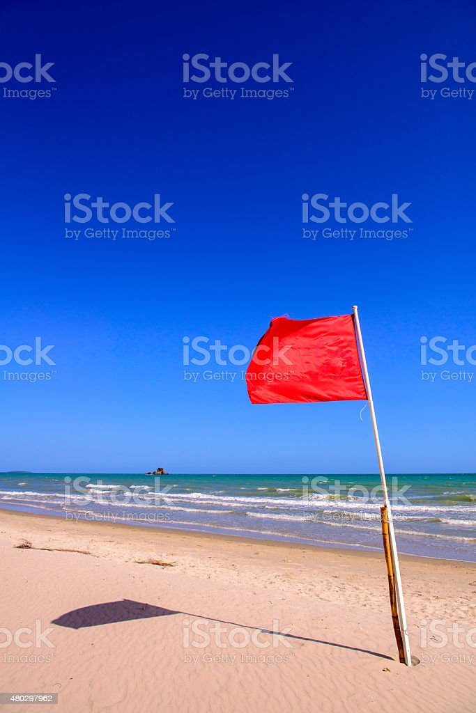 Red warning flag on a beach stock photo