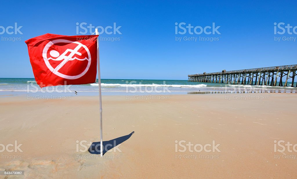 Red Warning Flag on Beach stock photo