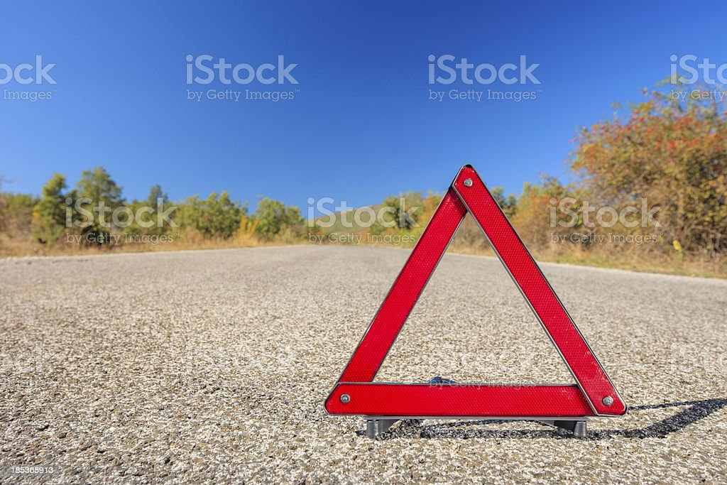 Red warning triangle on a road royalty-free stock photo