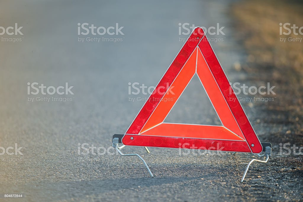 Red warning triangle on a road suggesting a broken down car stock photo