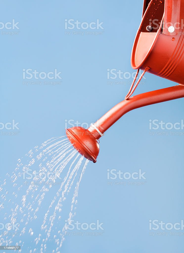 Red Watering Can Pouring, Sprinkling, Flowing Water Against Blue Sky stock photo