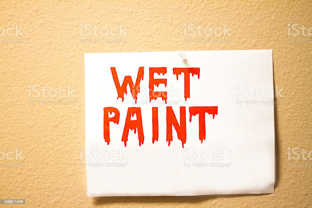 Red 'WET PAINT' Sign on Yellow Wall; Copy Space stock photo