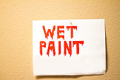 Red 'WET PAINT' Sign on Yellow Wall; Copy Space