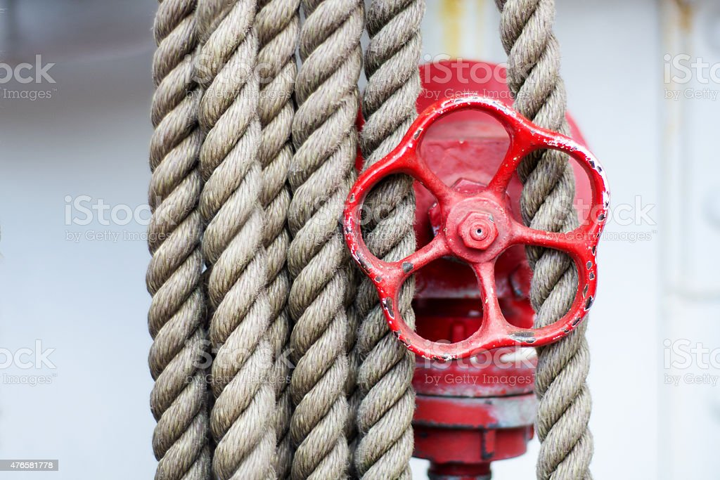red wheel, stop valve and ropes on a Tall Ship stock photo