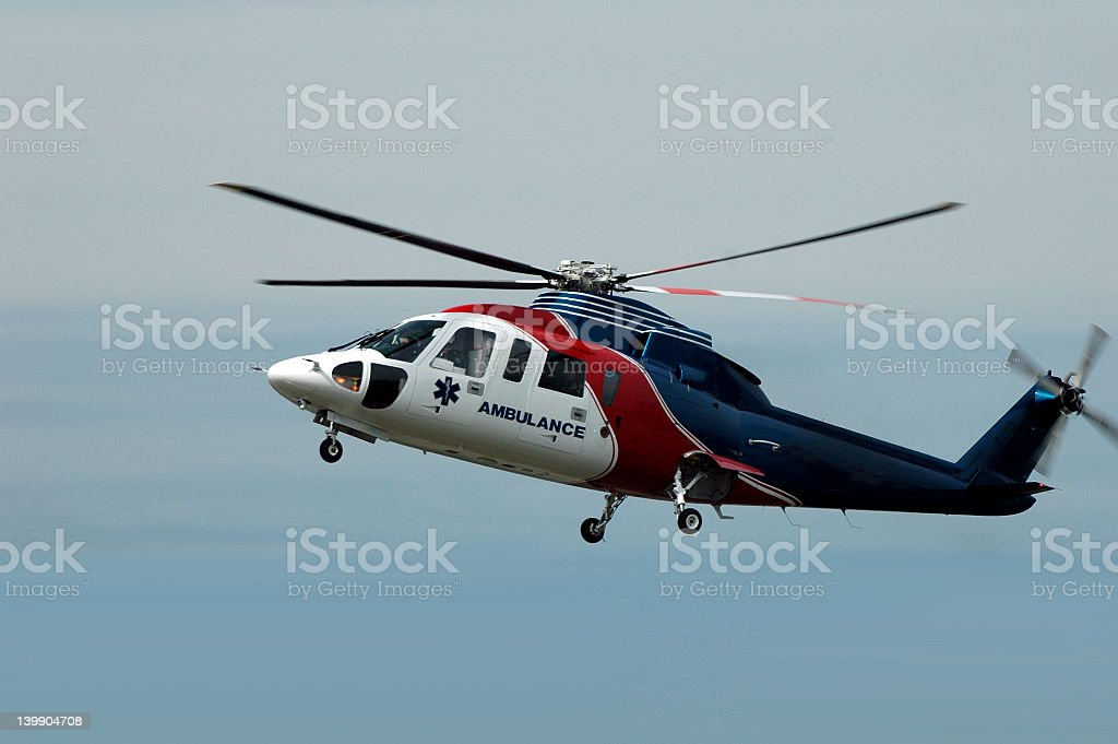 A red, white and blue air ambulance helicopter stock photo