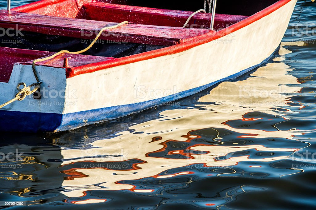 red white and blue rowboat with reflections in water ripples stock photo