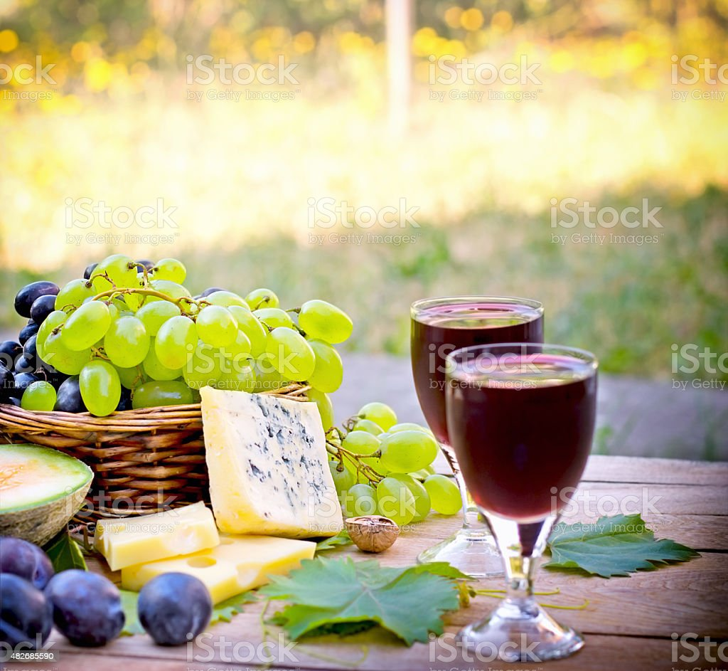Red, white grapes, cheese and red wine for your enjoyment stock photo