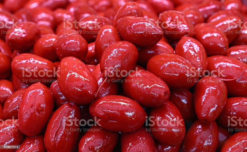 Red whole Cerignola olives in oil close up stock photo