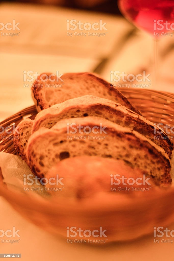 Red wine and basket of bread on a table, Italy stock photo