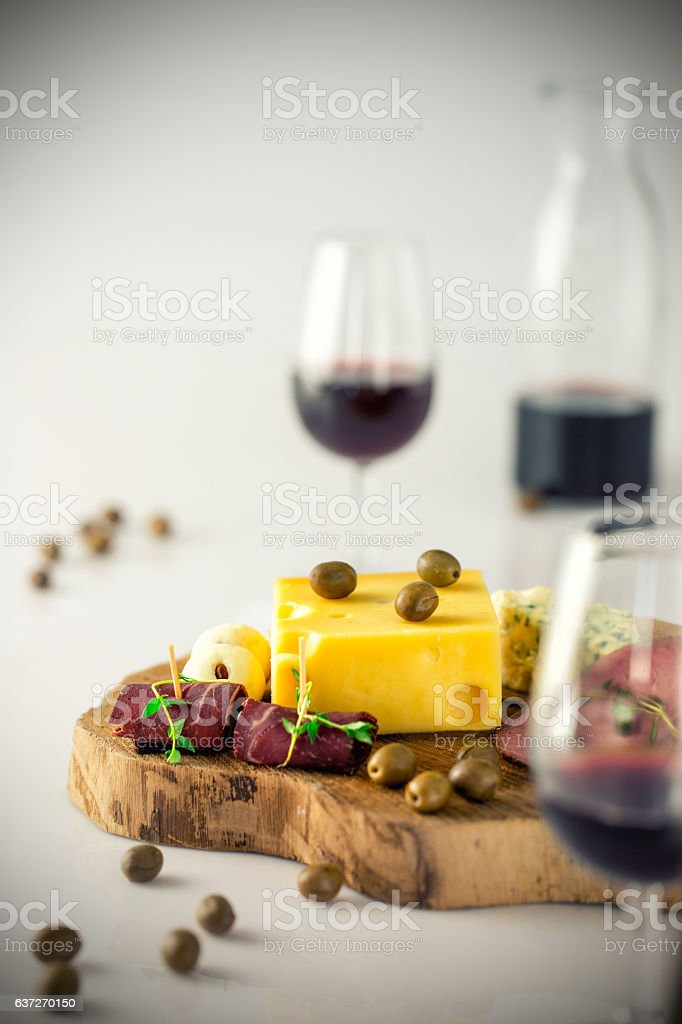 Red wine and cheese platter on white background stock photo