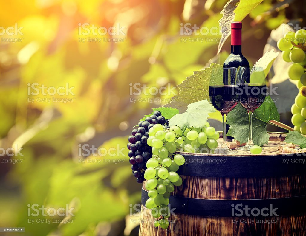 Red wine and glass on wodden barrel. stock photo