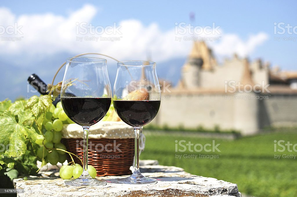 Red wine and grapes against an old castle. Switzerland stock photo