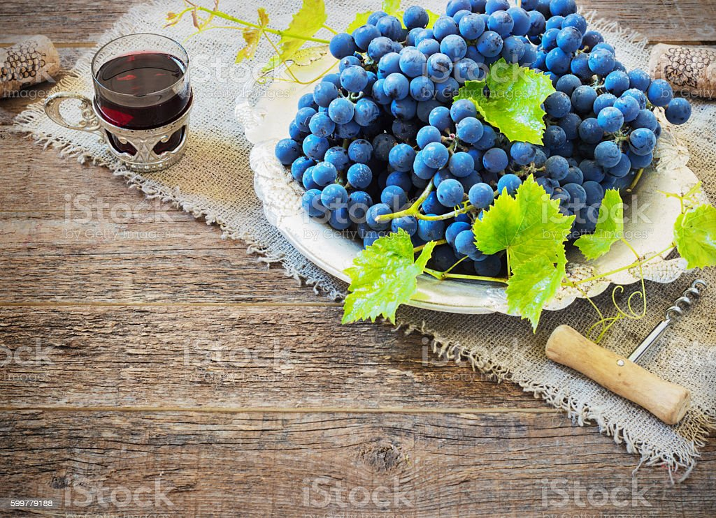 red wine and grapes in vintage setting with corks stock photo