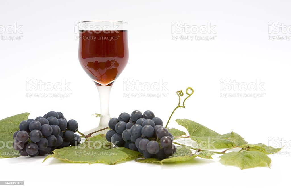 Red wine and grapes on leaf royalty-free stock photo