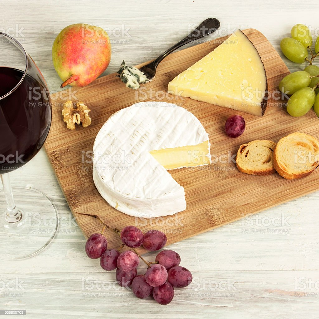 Red wine and selection of cheeses with grapes stock photo