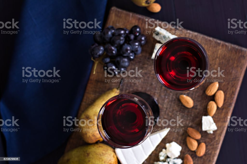 Red wine and snacks. Wine, grapes, cheese, nuts, olives. Romantic evening, still life. stock photo