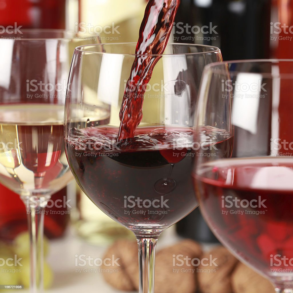 Red wine being poured into a glass surrounded by other wine stock photo