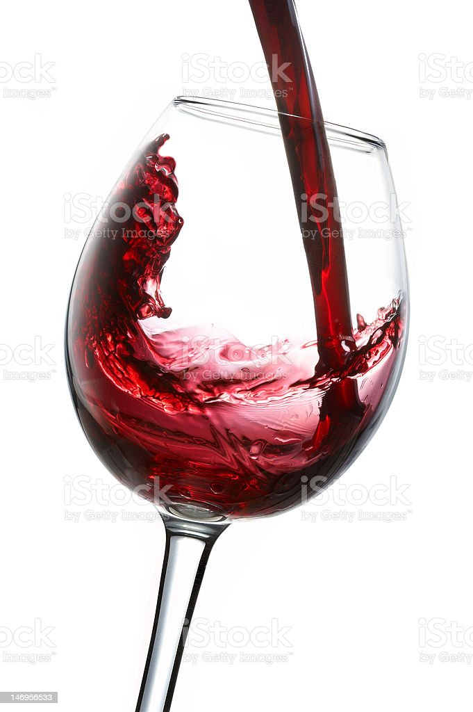 Red wine being poured into glas, isolated on white royalty-free stock photo