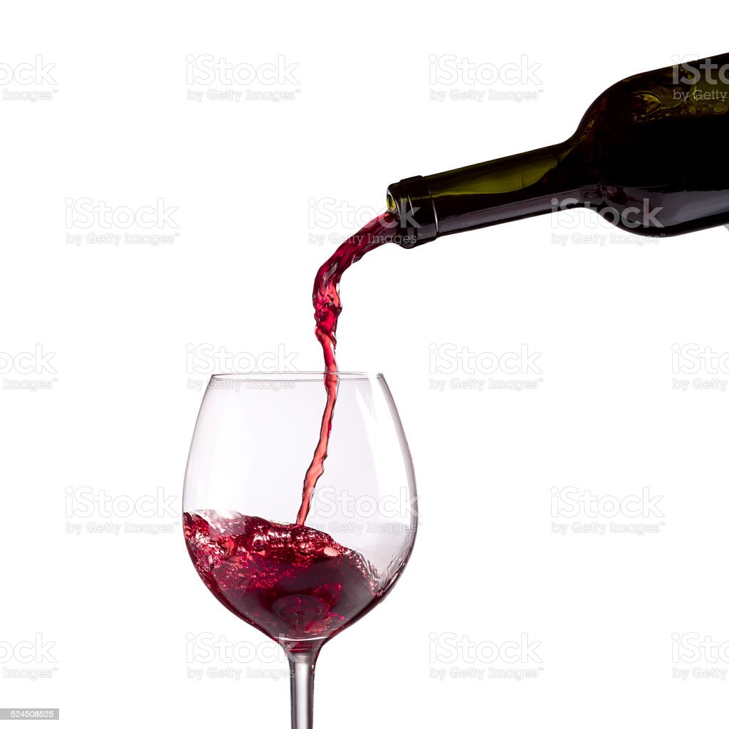Red wine being poured into wine glass on white background stock photo