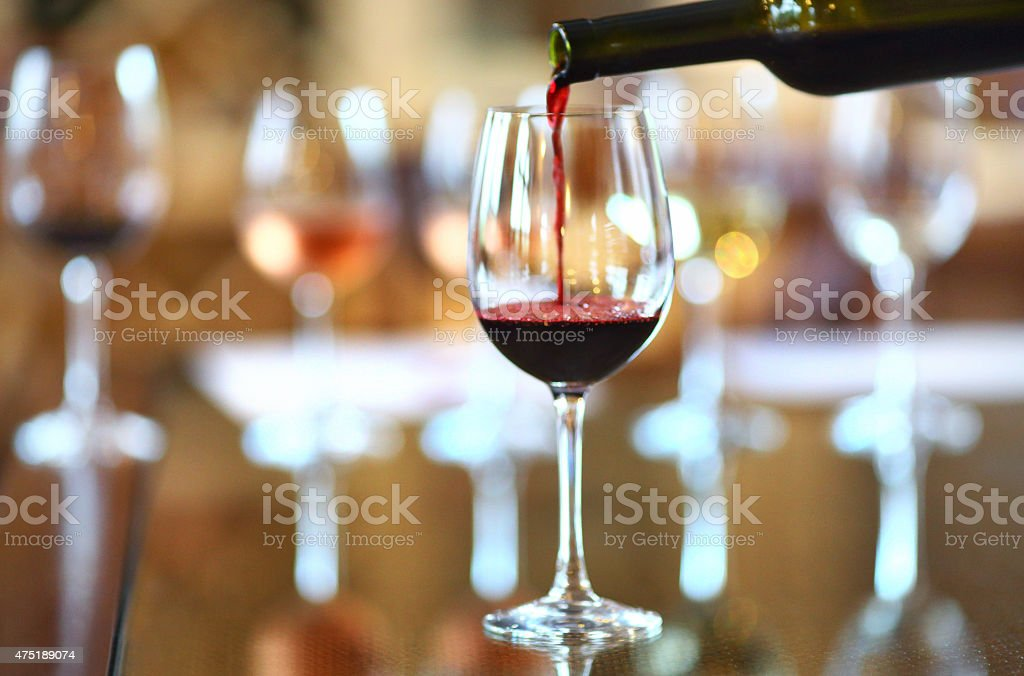 Red wine being poured into wineglass. stock photo