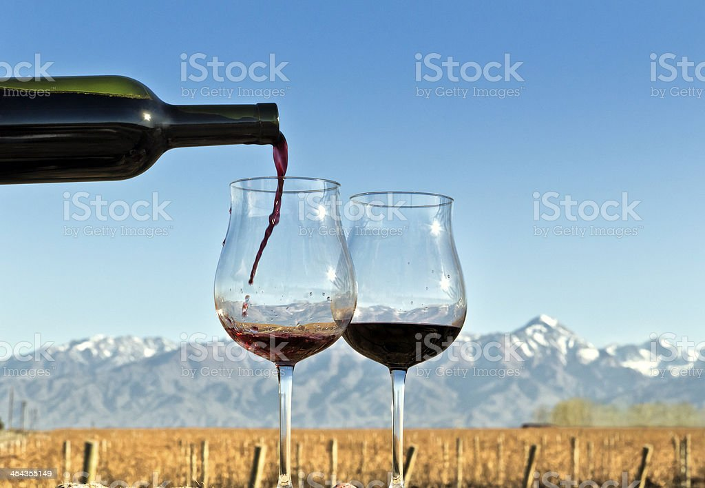 Red wine being poured with a mountain range in the back royalty-free stock photo