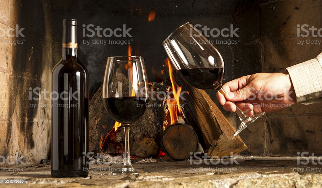 Fireplace Design fireplace background : Red Wine Bottle And Cups With Hand Cheers Fireplace Background ...