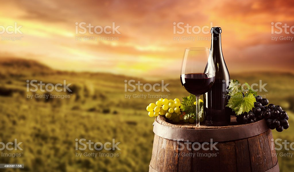 Red wine bottle and glass on wodden keg stock photo