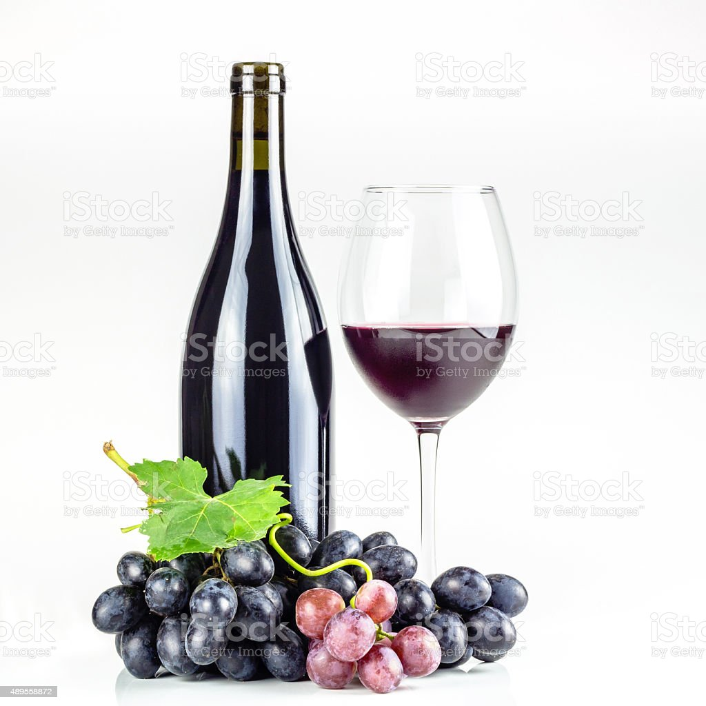 Red wine bottle, wineglass and grapes. stock photo