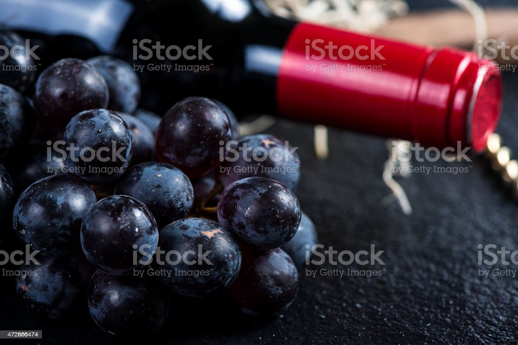 Red wine bottle with grapes and corkscrew stock photo