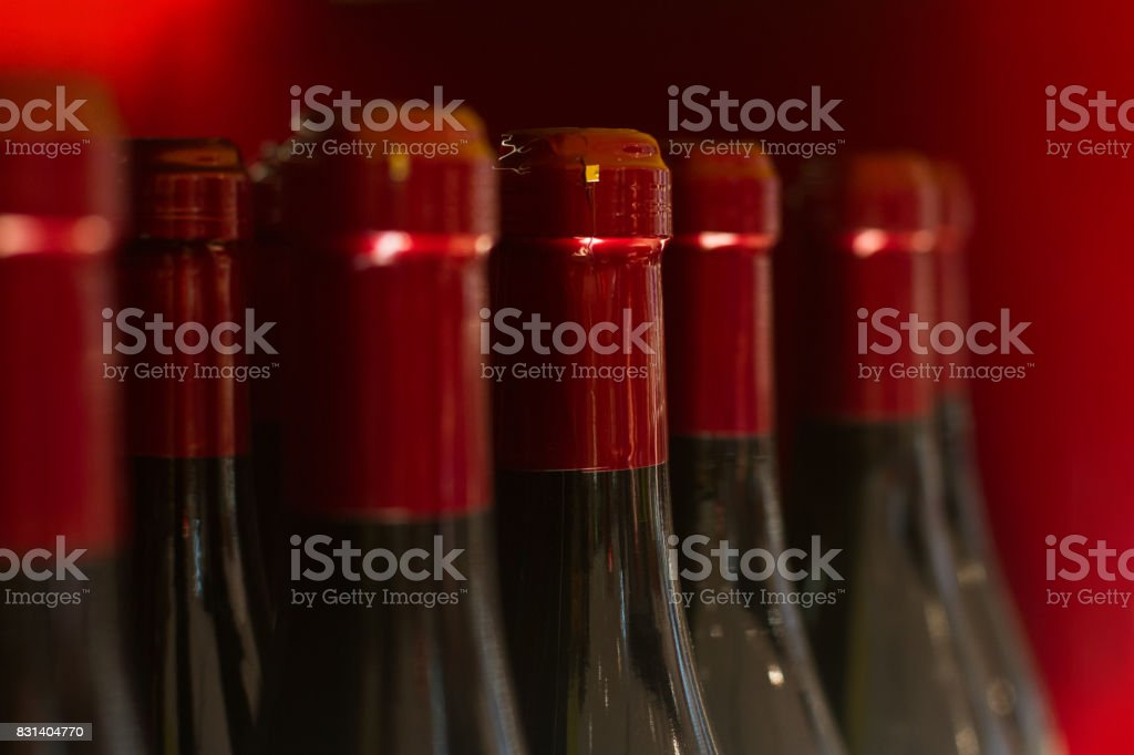 red wine bottles in store stock photo