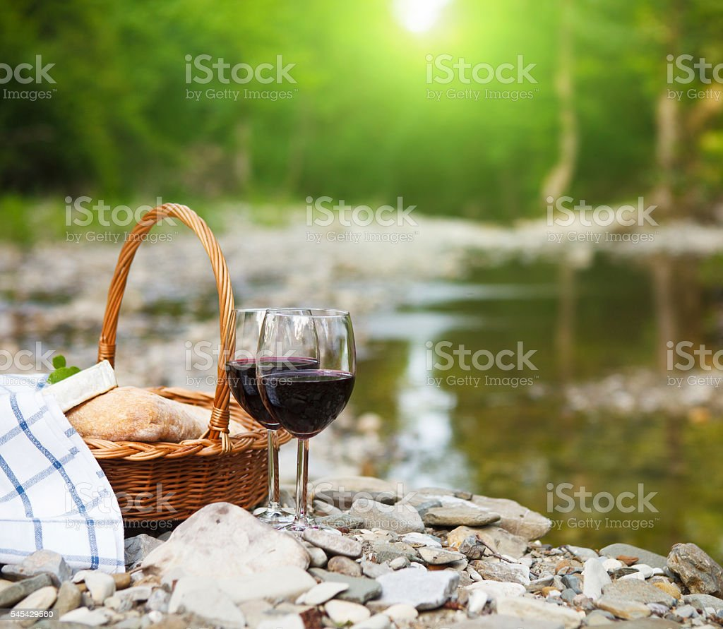 Red wine, cheese and bread served at a picnic stock photo