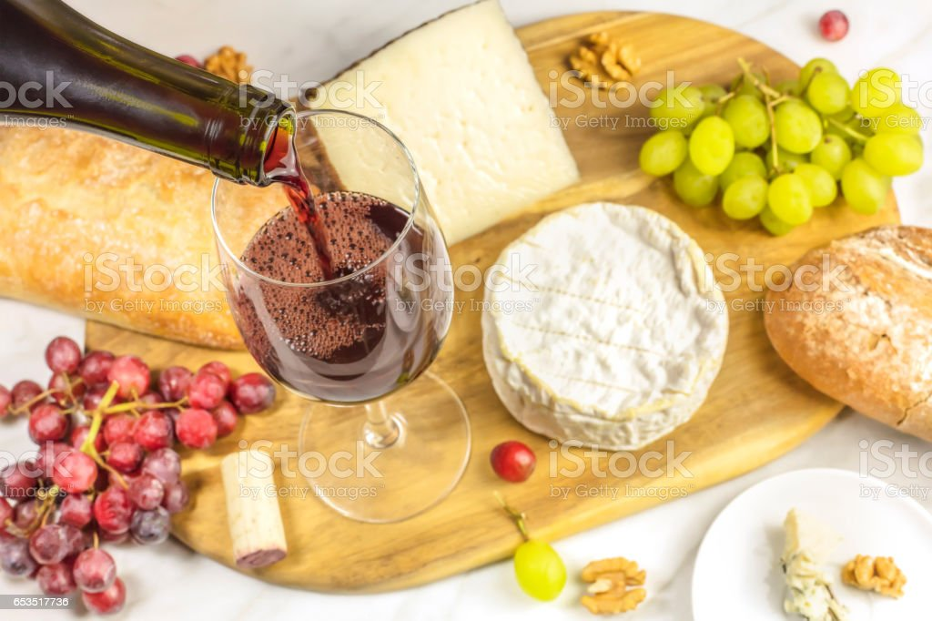 Red wine, cheese, bread and grapes at tasting stock photo