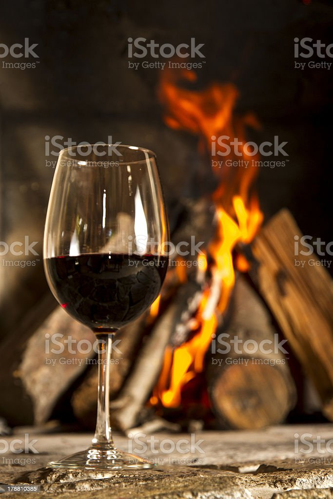 Red wine cup glass with fireplace on the background. royalty-free stock photo