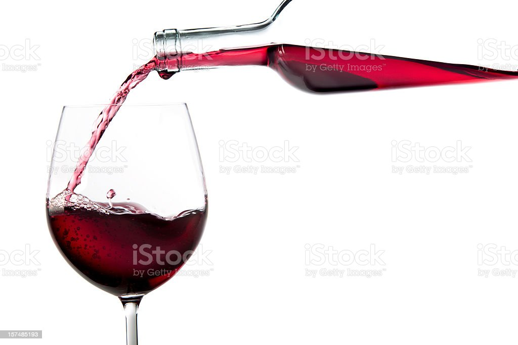 red wine falling from bottle to glass isolated on white stock photo