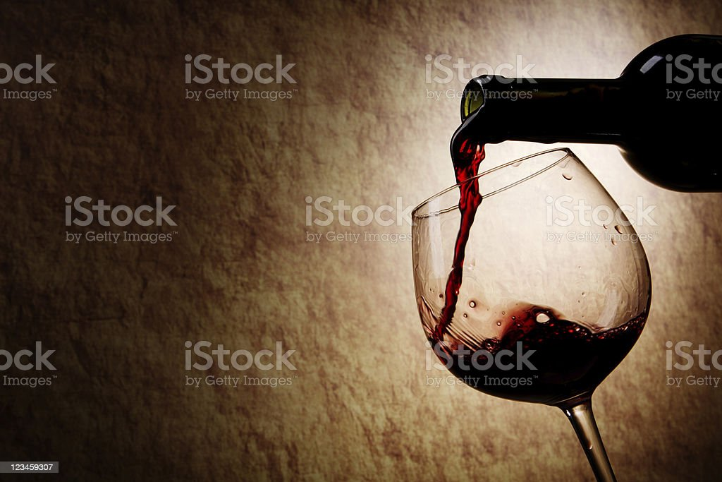Red Wine glass and Bottle on a old stone background stock photo