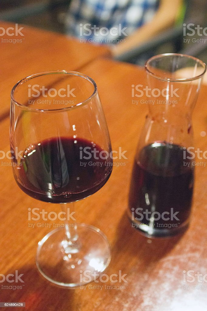 Red wine glass and carafe on a table stock photo