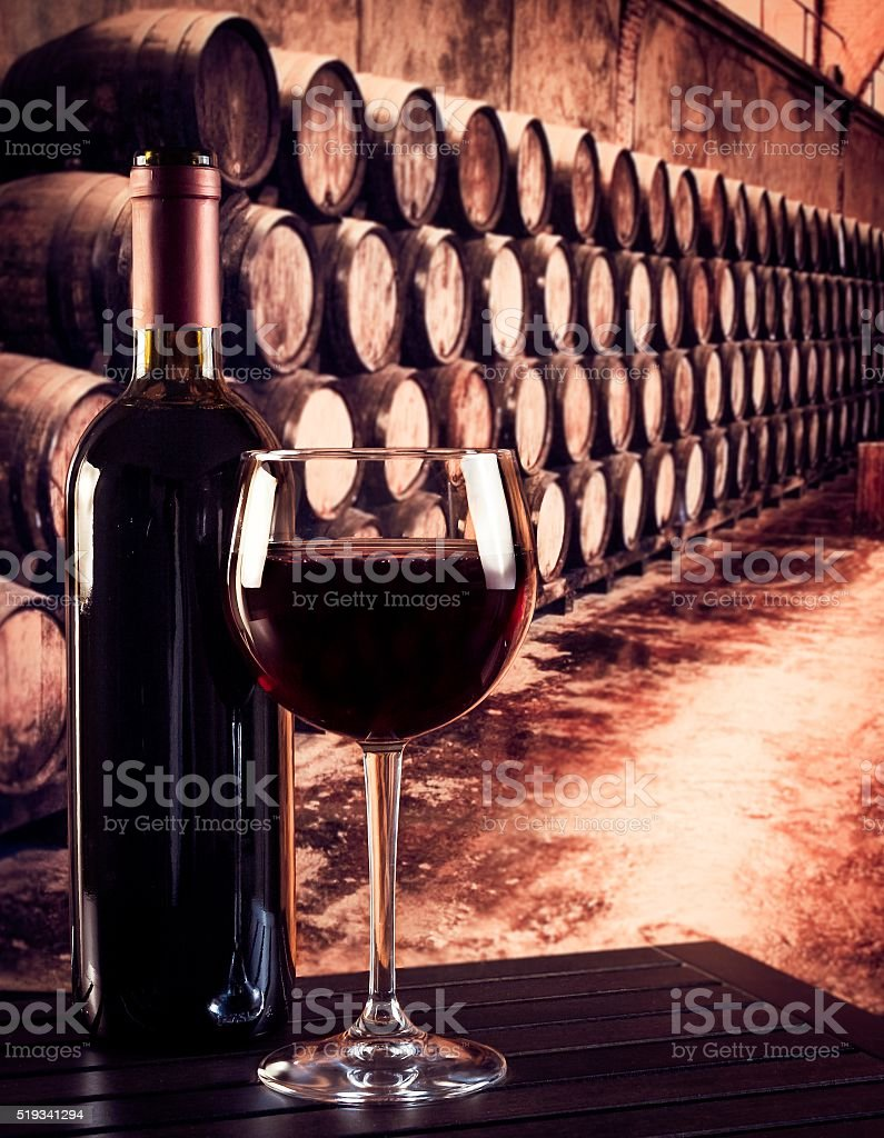 red wine glass near bottle in old wine cellar background stock photo