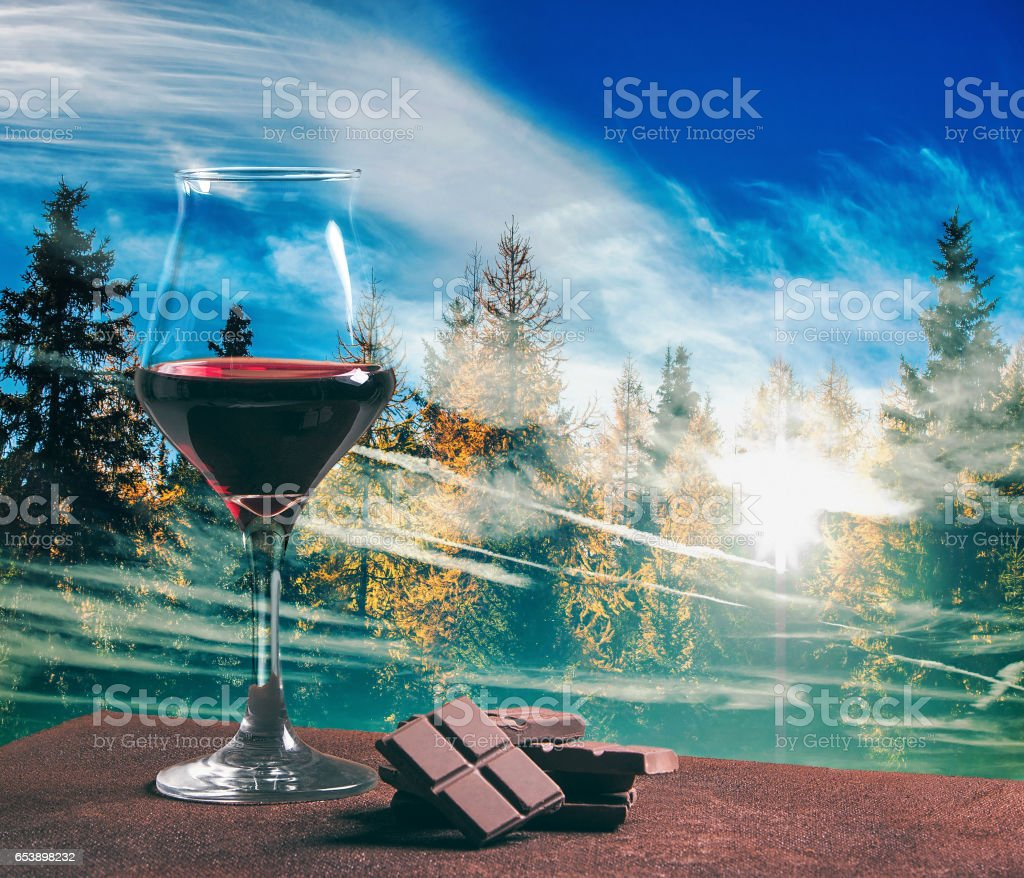 Red wine glass with chocolate and autumn wood with cloudscape stock photo