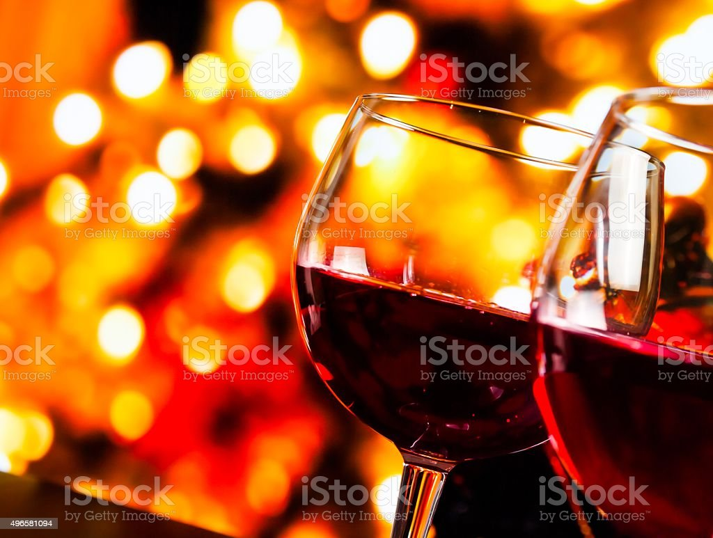 red wine glasses against colorful unfocused lights background stock photo